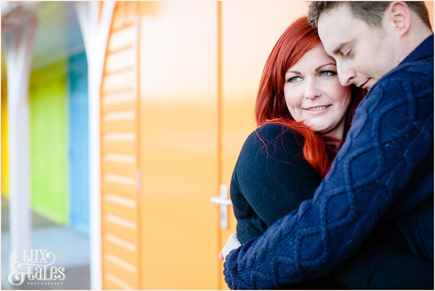 Couple cuddles inf ront fo beach huts in scarborough at North BEach