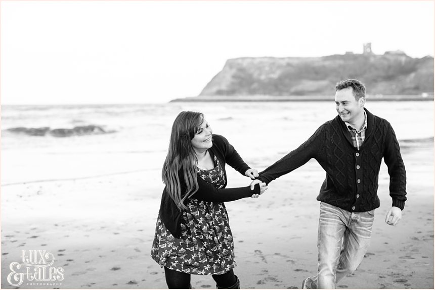 Fun couple play at the beach in scarborough engagement shoot