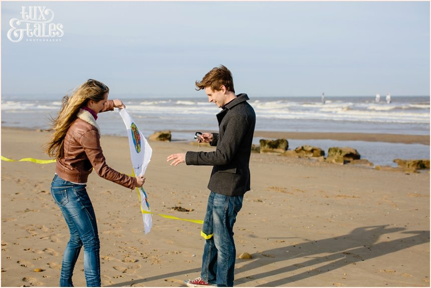 Engaged couple fly a kite at fristhorpe beach
