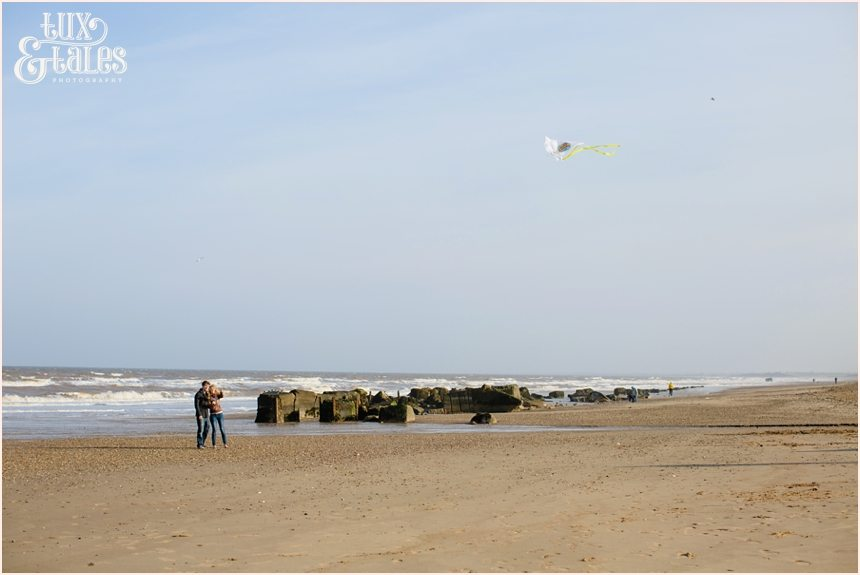 engaged couple fly a kite at Fraisthorpe beach