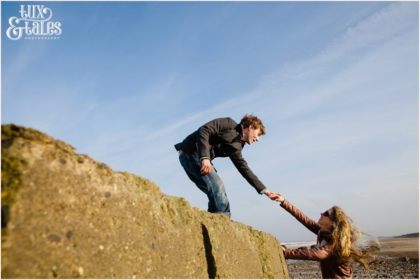 Cute engaged couple climb on bunker at Fraisthorpe beach engagement shoot