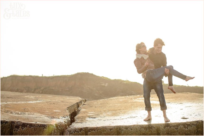 playing on the bunker in the sunset at Fraisthorpe beach engagement shoot