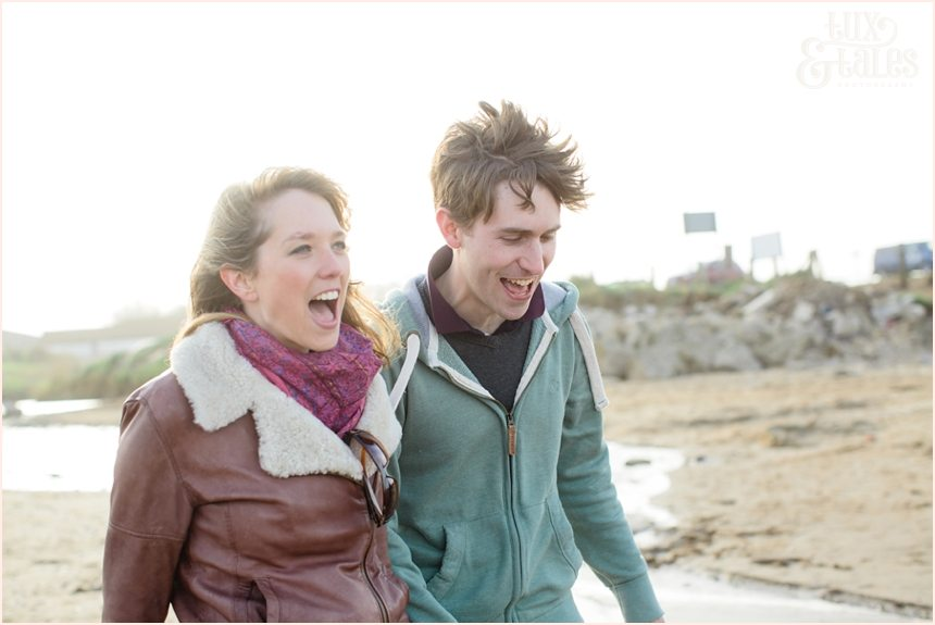 laughing and smiling couple at engagement shoot at Yorkshire beach