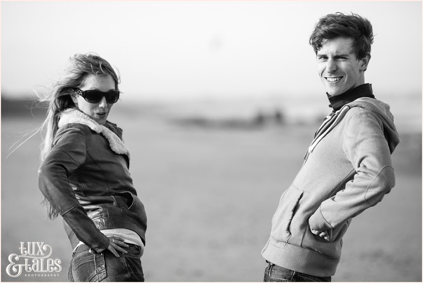 couple makes silly faces at Yorkshire beach engagement shoot