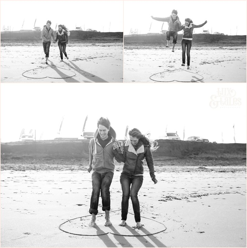 couple laughing and jumping at yorkshire beach engagement shoot at Fraisthorpe beach