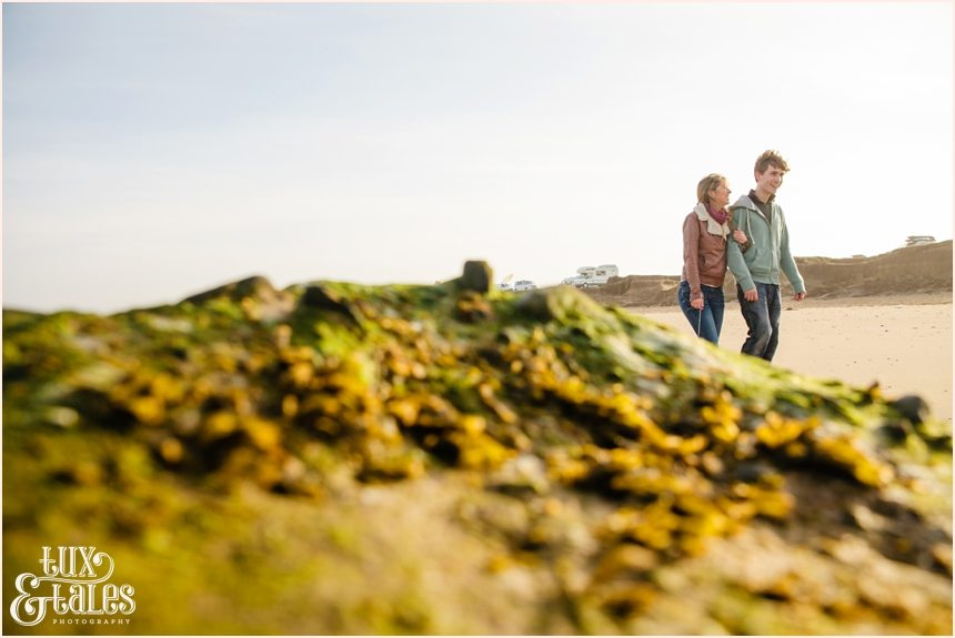 couple walks on the beach during engagement shoot