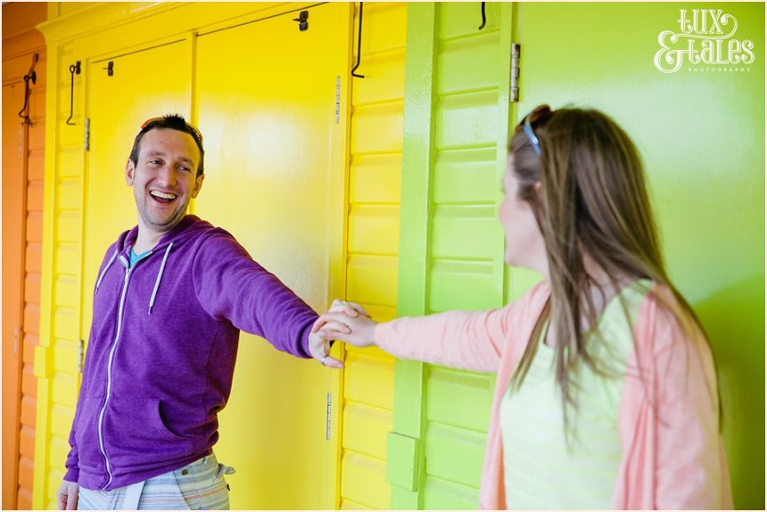Eun engagement photography with colourful beach huts at North Beach Scarborough Yorkshire