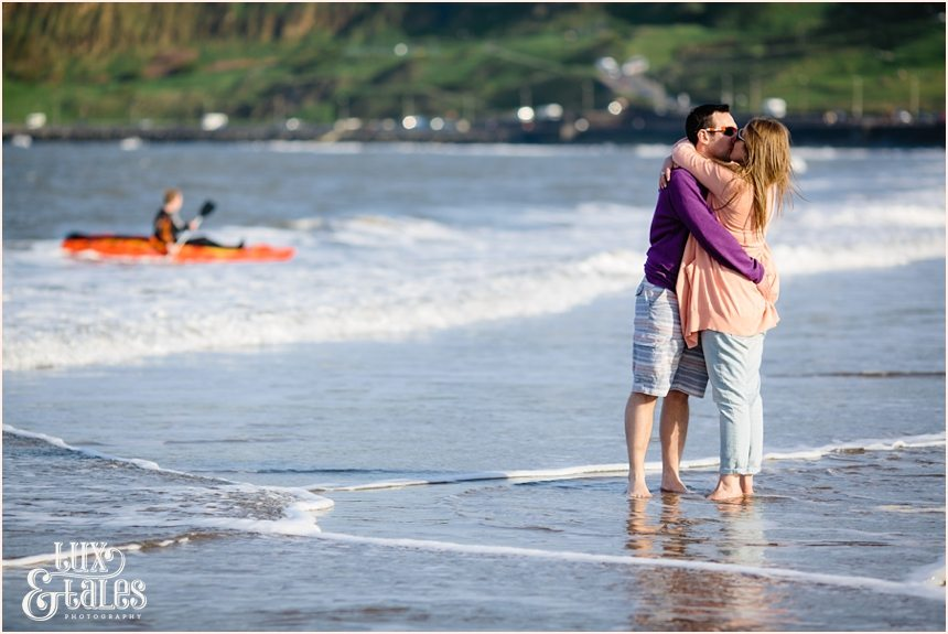 Couple hugging in the waves in North Beach engagement photography session