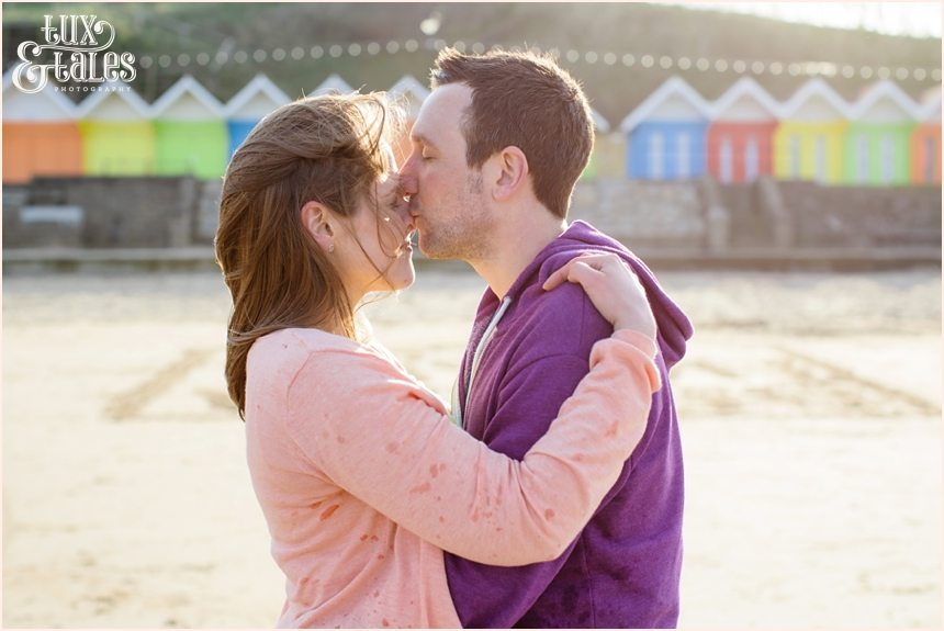 Couple kidding in front of the rainbow beach huts in Scarborough engagement photography