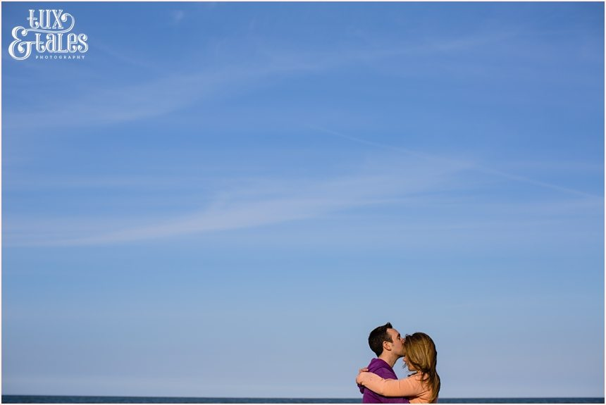 Scarborough engagement photography couple cuddling in front of blue sky