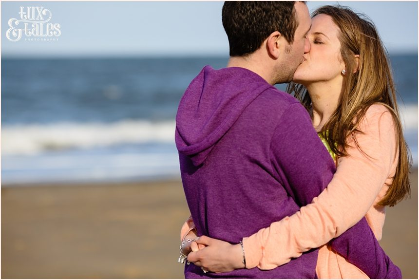 Couple kissing in front of the beach at North Beach Scarborough