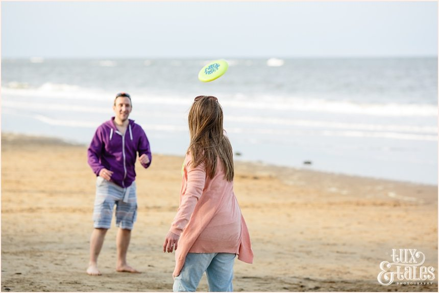 Tossing the frizbee at scarborough engagement photography session at the beach