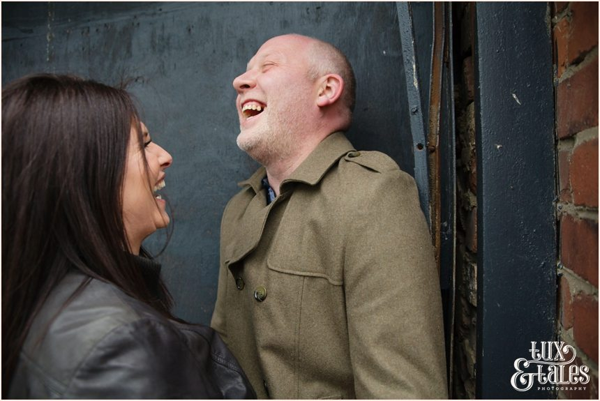 Couple laughing in fornt of black wall in Granary Wharf, Leeds