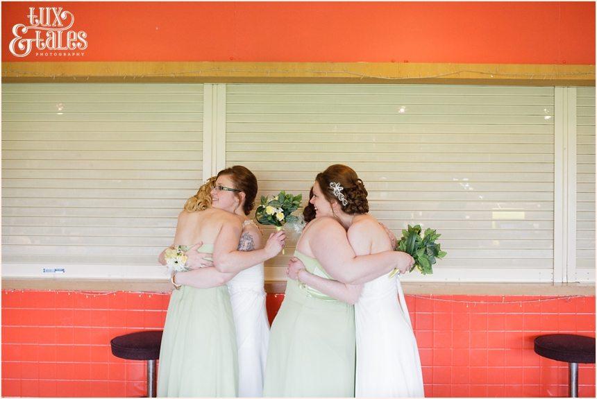 Two brides hug their bridesmaids