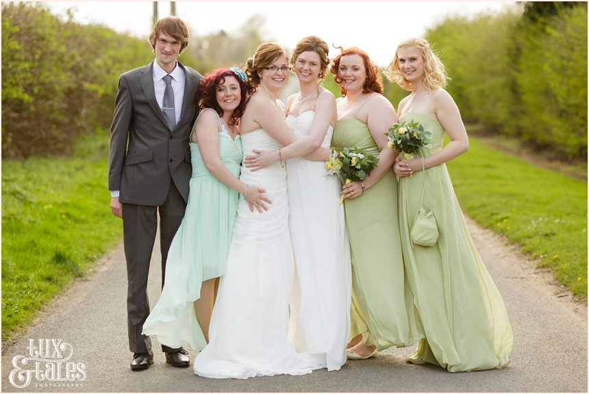 Two brides and bridal party with sage green wedding dresses
