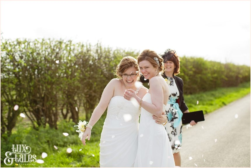 Laughing brides with confetti
