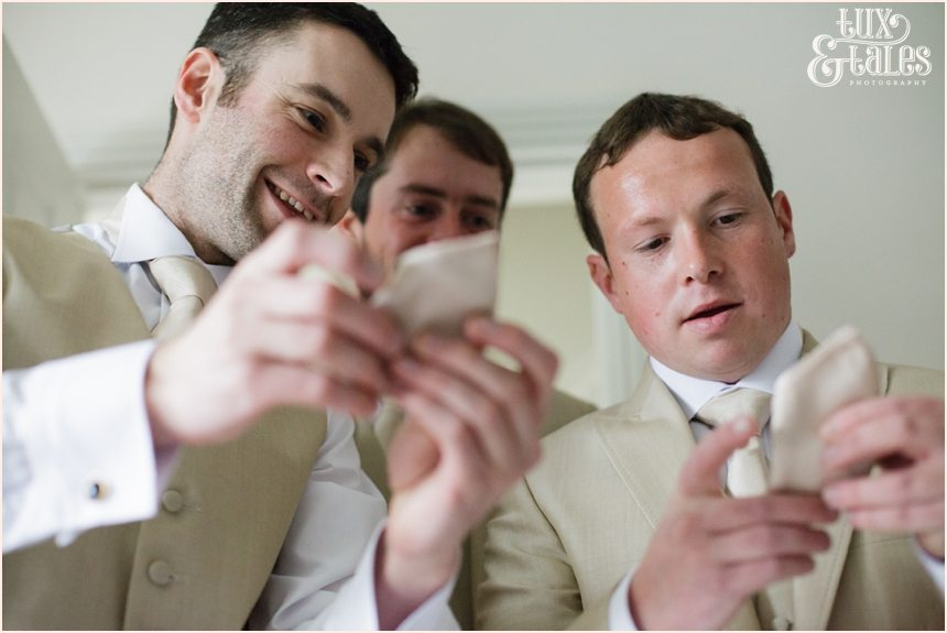 The guys examine their ties at a yorkshire wedding