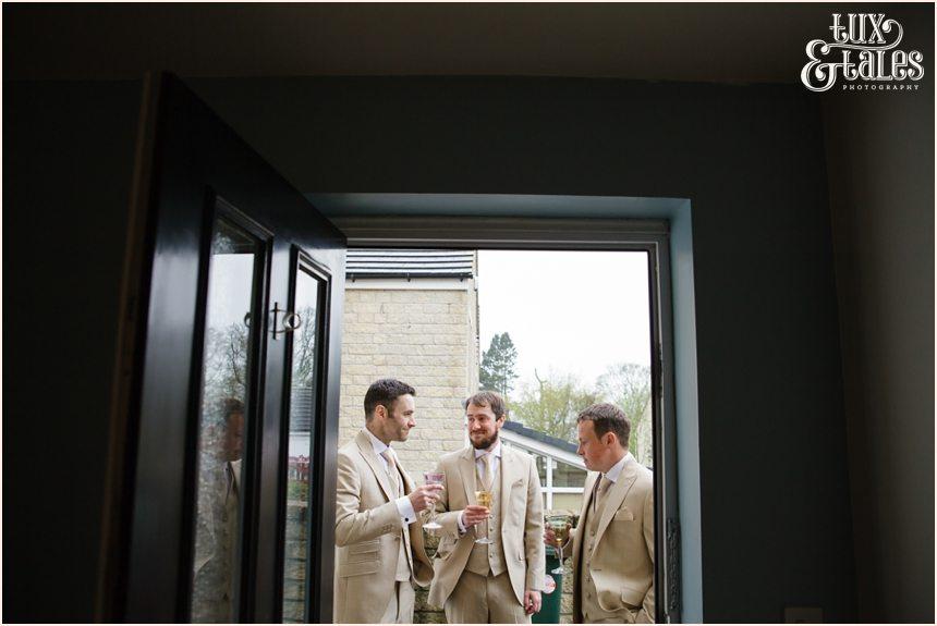 Groomsmen stand outside framed by door in Yorkshire wedding