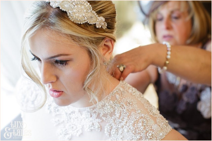 mother of the bride helps the bride get ready at yorkshire wedding