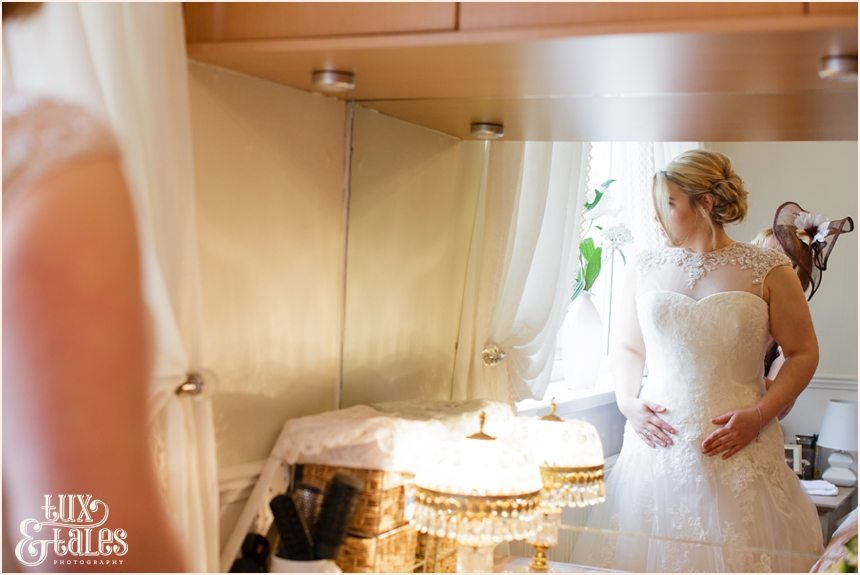 bride looks out window as her dress is fastened at yorkshire wedding
