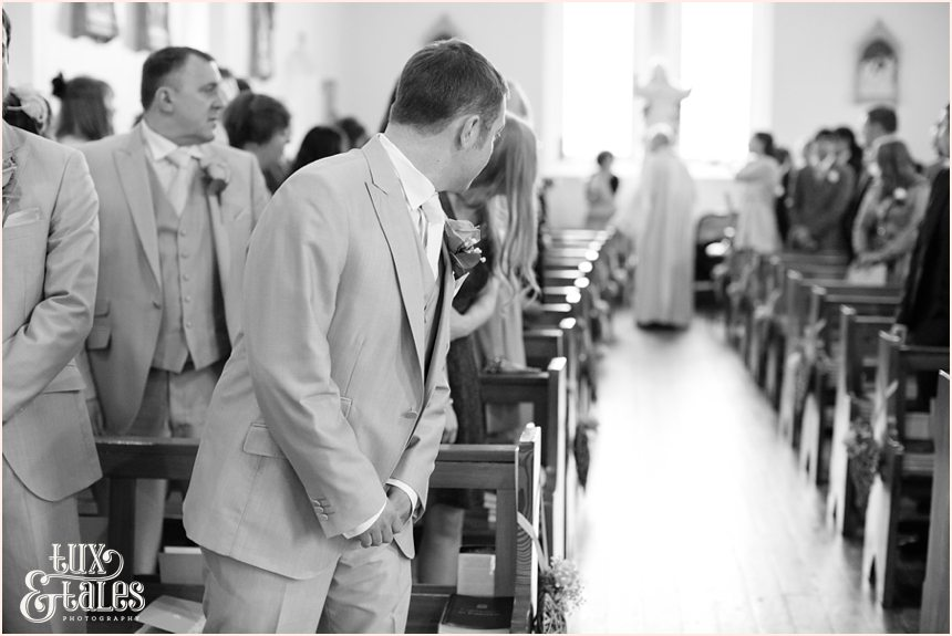 Groom looks down the aisle waiting for bride at yorkshire wedding