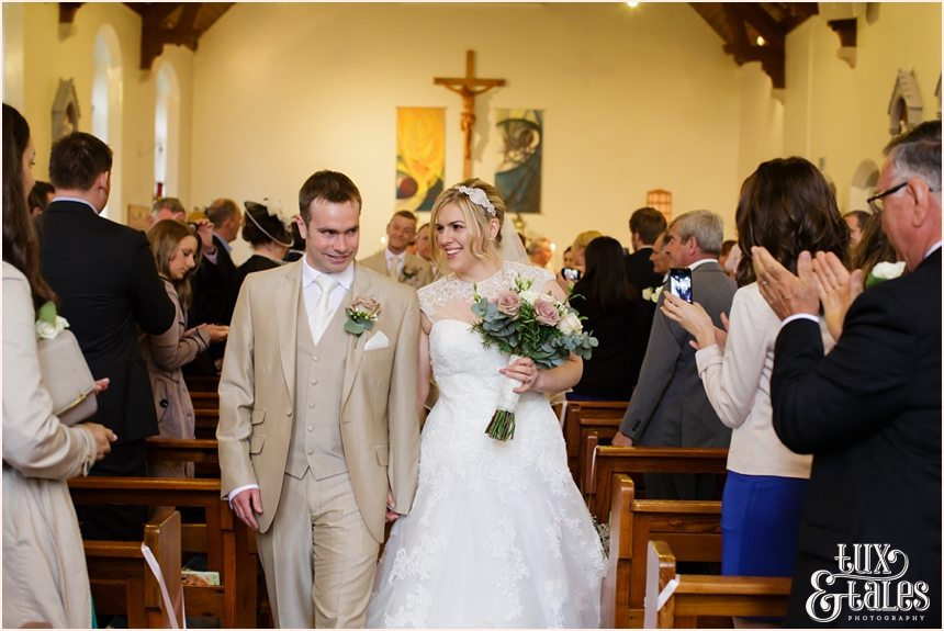 Bride and groom walk up the ailse at yorkshire wedding