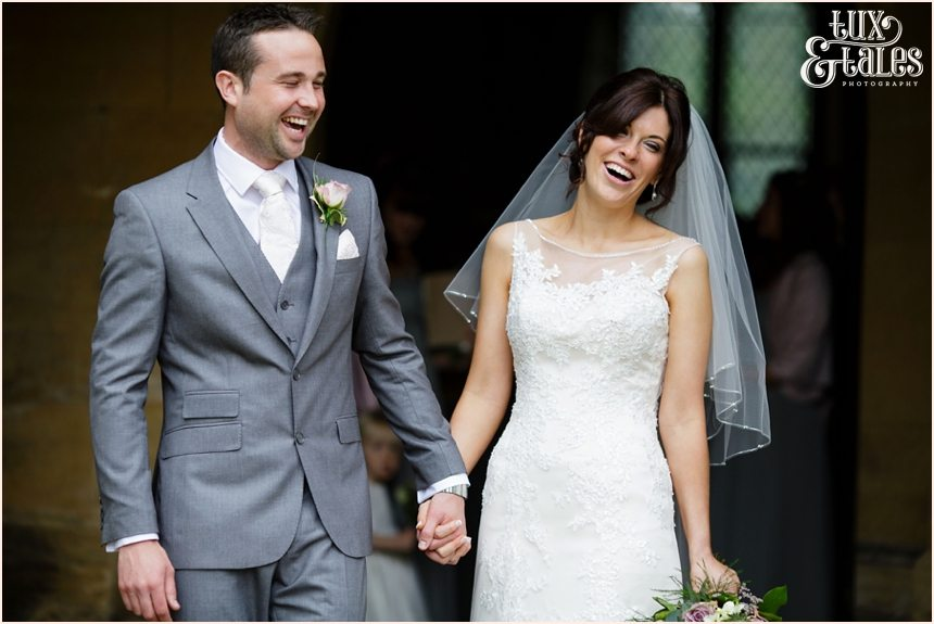 Bride and groom walk out of escrick church smiling