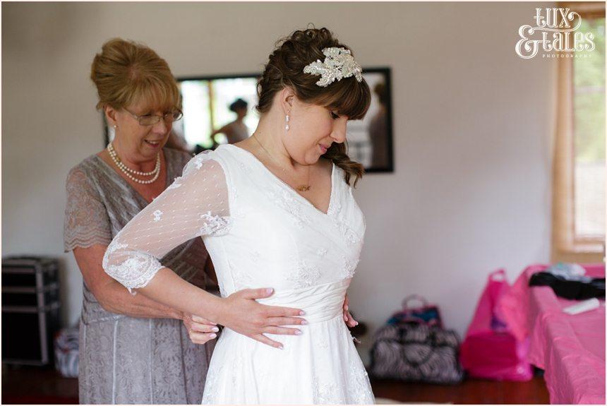 bride puts on lace wedding dress altrincham wedding