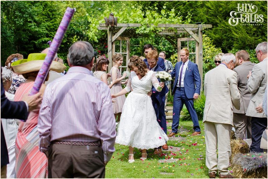 Bride and groom conga line up the aisle at Althrincham back garden wedding Tux & Tales Photography
