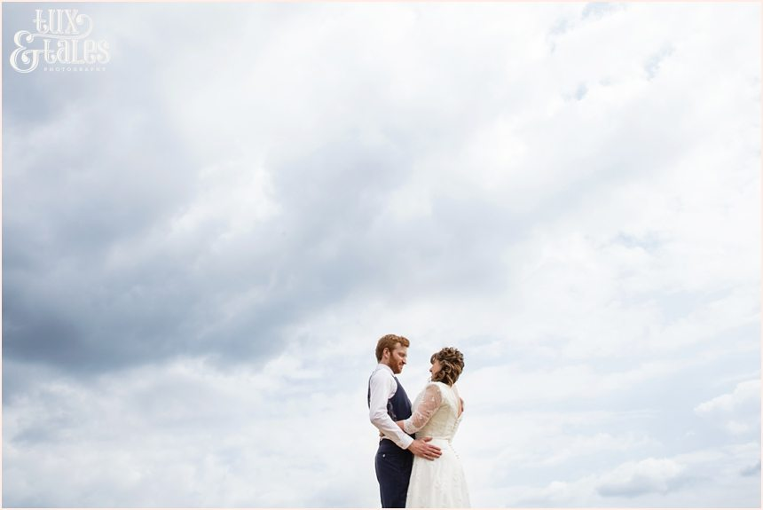 Bride and groom in an althrincham field. Tux & Tales Photography relaxed and natural photos