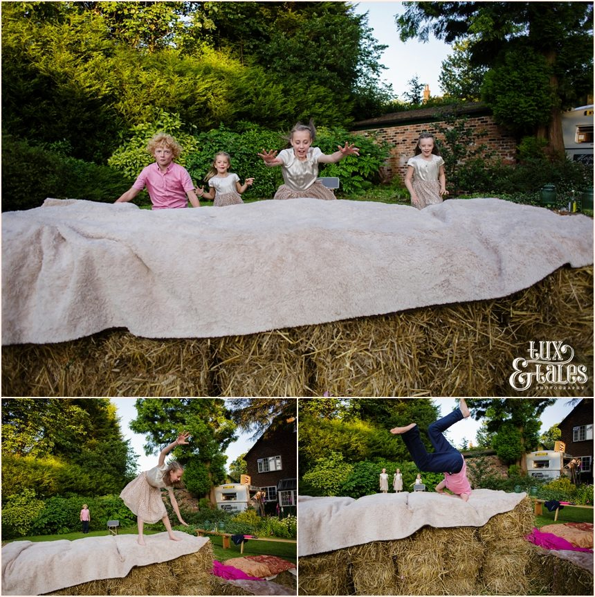 Kids playing on hay bales at Tipi wedding in back garden in Altrincham