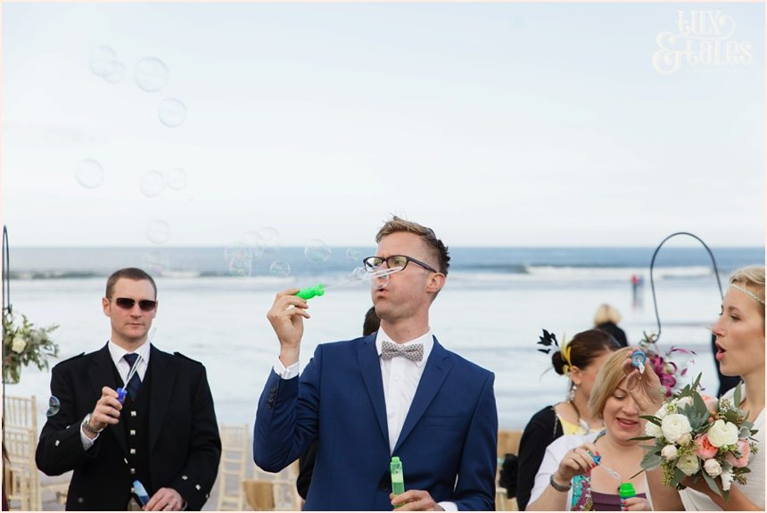 Ceremony Photography at Newton Hall beachside wedding | Guest Blowing Bubbles