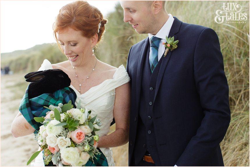 Bride & Groom Portraits in the rain at Newton Hall beachside wedding photography | Holding bunny