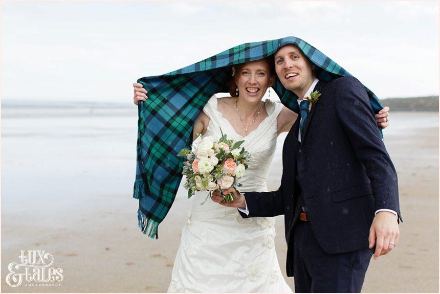 Bride & Groom Portraits in the rain at Newton Hall beachside wedding photography | Hiding under tartan shawl