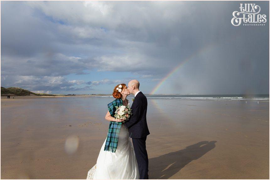 Bride & Groom Portraits in the rain at Newton Hall beachside wedding photography | Kissing under rainbow
