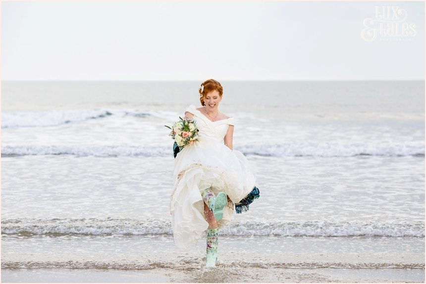Bride & Groom Portraits in the rain at Newton Hall beachside wedding photography | Bride kicking up water in wellies