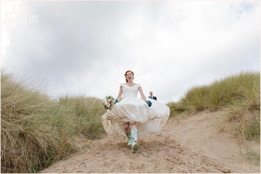 Bride & Groom Portraits in the rain at Newton Hall beachside wedding photography | Running down sand dune