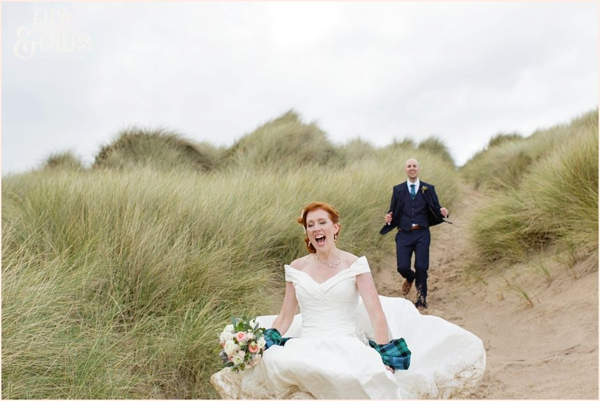 Bride & Groom Portraits in the rain at Newton Hall beachside wedding photography | Running down sand dune