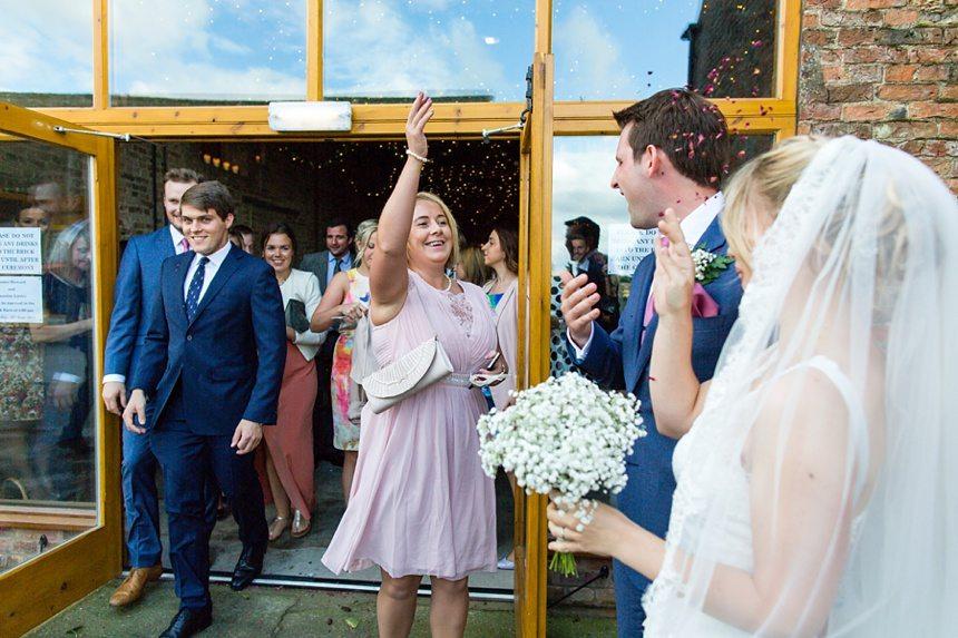 Guest throwing confetti Barmbyfield Barn Wedding