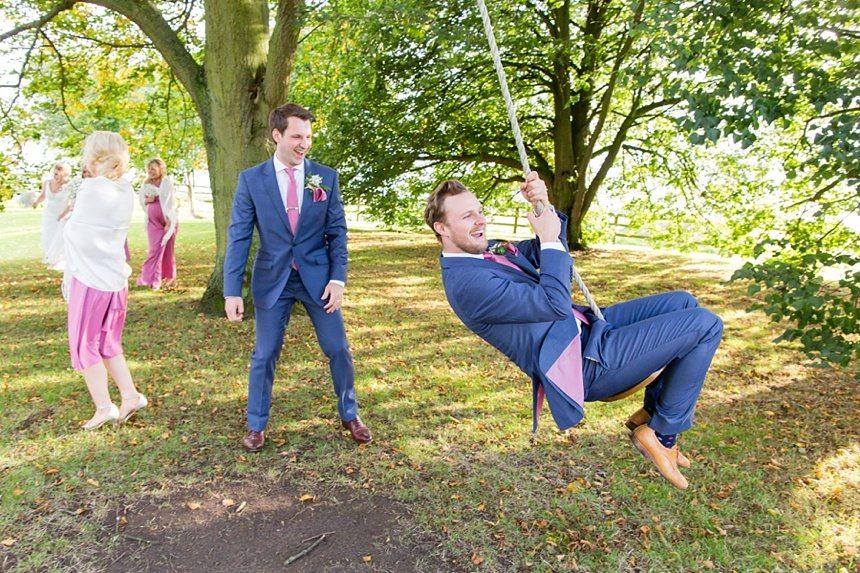 Groom pushing best man on swing
