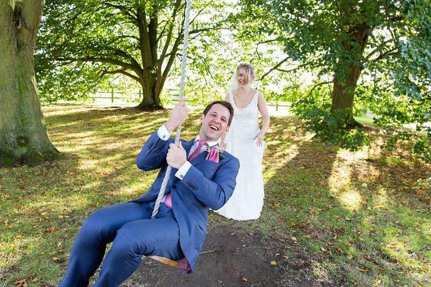Bride pushing groom on swing Barmbyfield Barn Wedding Photography