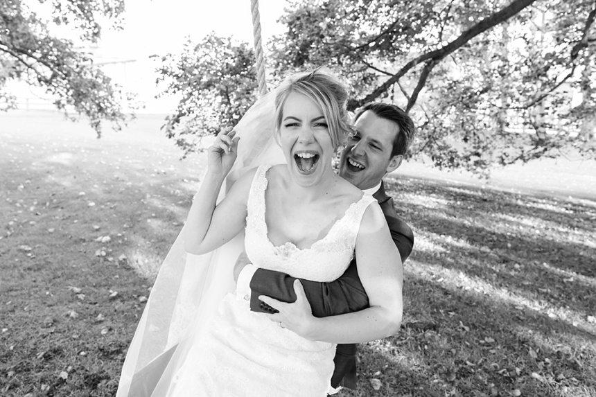 Bride sitting on groom's lap on swing Barmbyfield Barn Wedding Photography