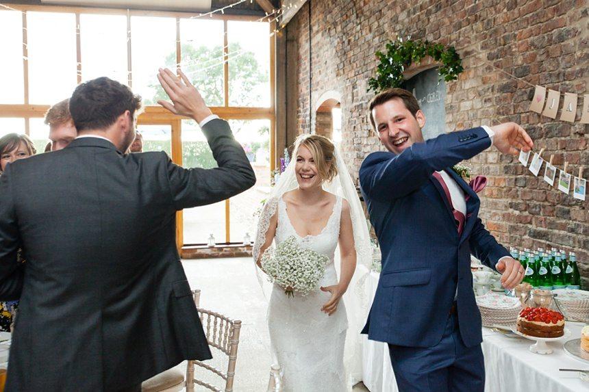 Bride & groom high 5 entrance Barmbyfield Barn Wedding Photography