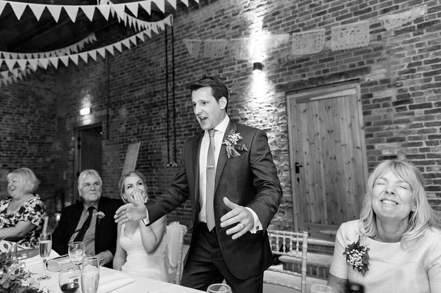 Groom making a funny expression during speech at wedding