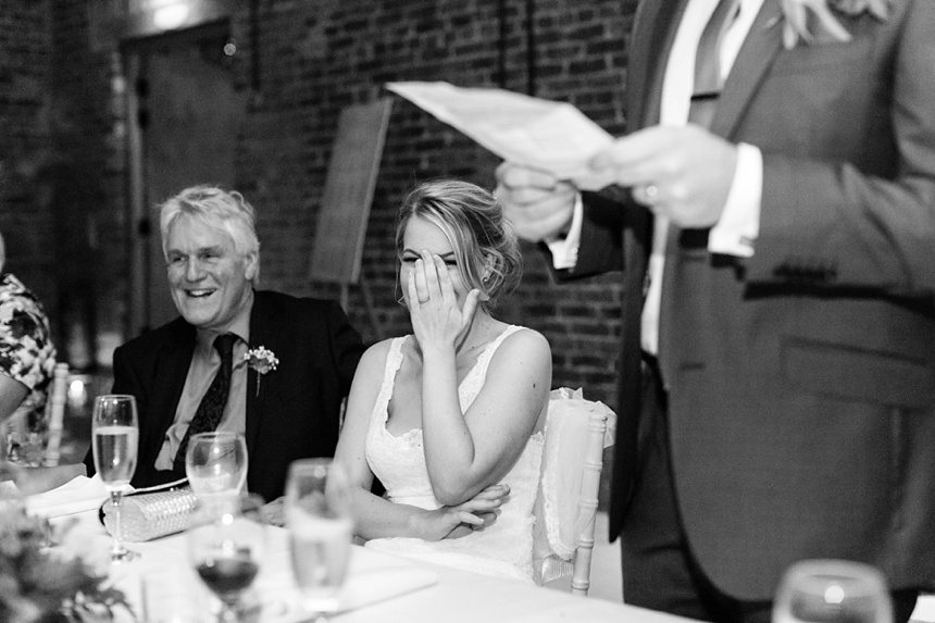 Bride covering face during embarassing moment at wedding speeches