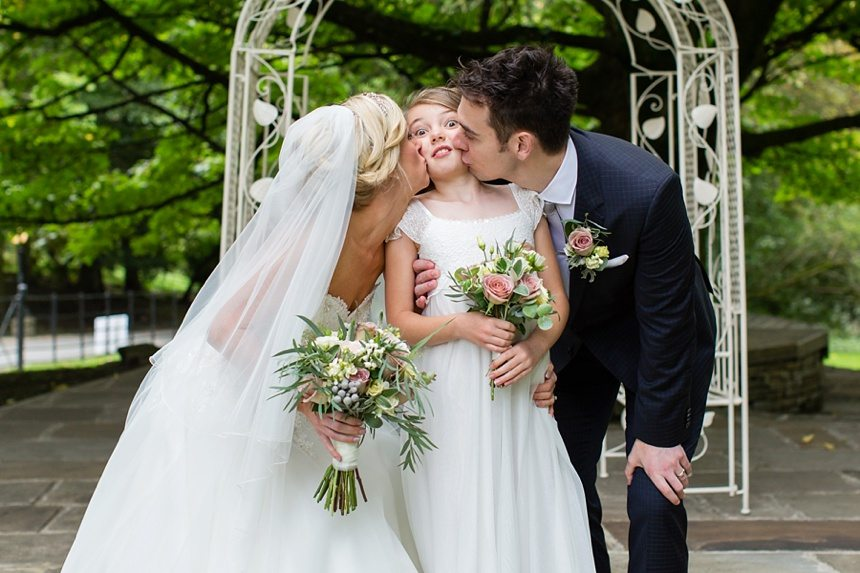 Bride & Groom kiss daughter at crow hill wedding