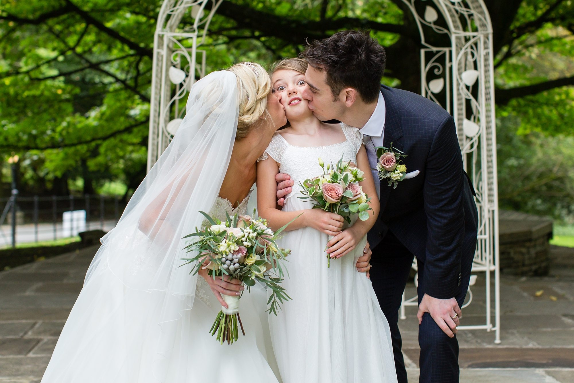 Funny photo of bride & groom kissing daughter