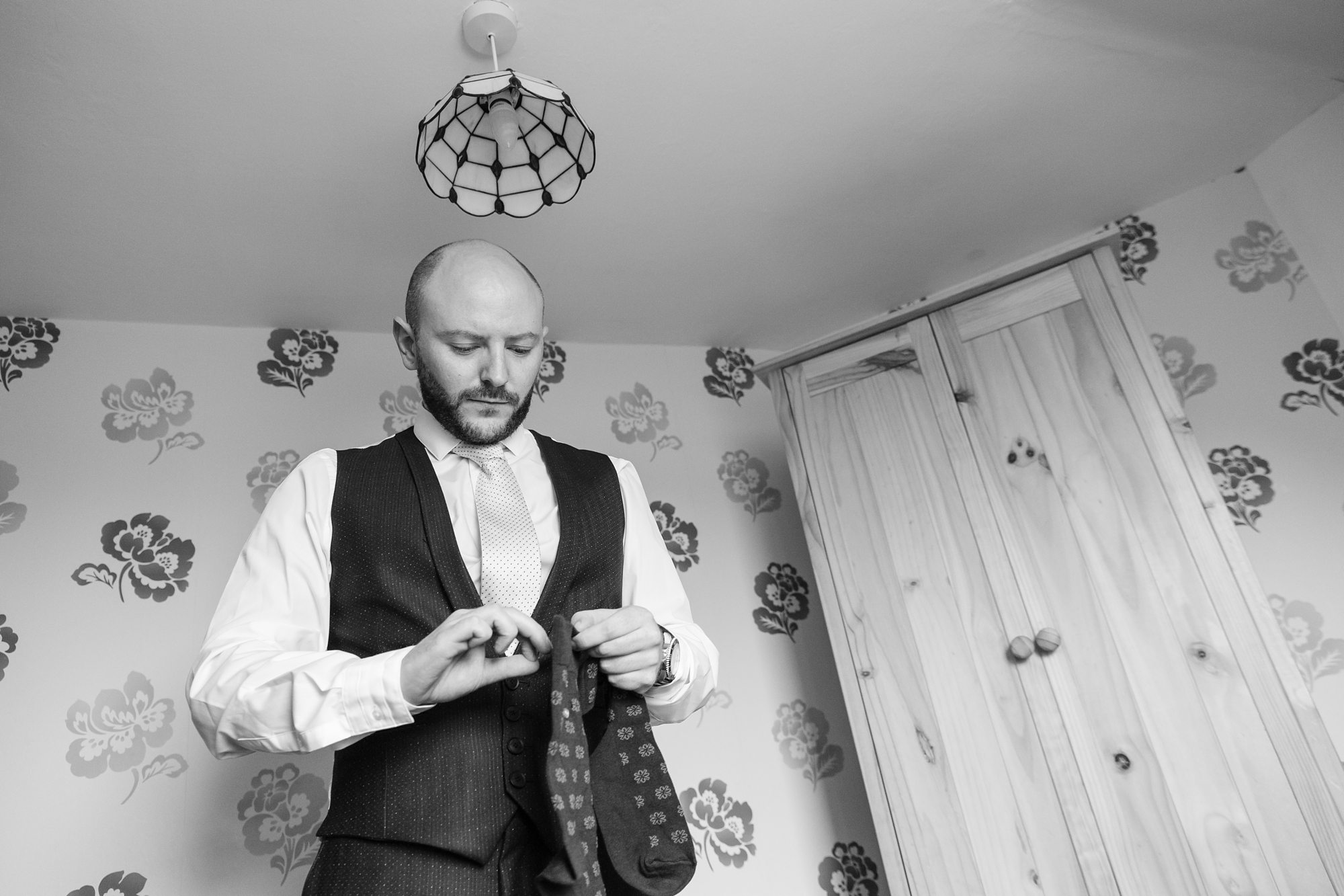 Groom holding socks in York Wedding in black and white