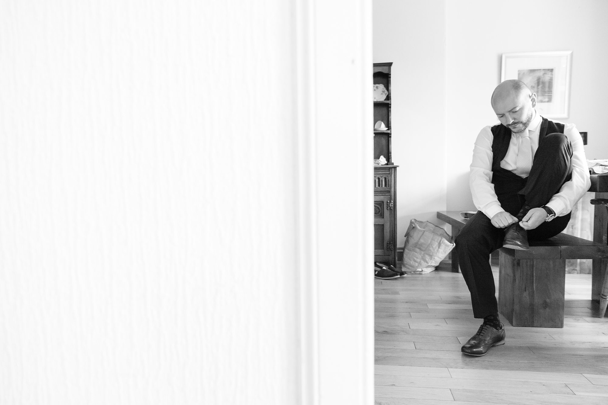 groom in black and white putting on shoes