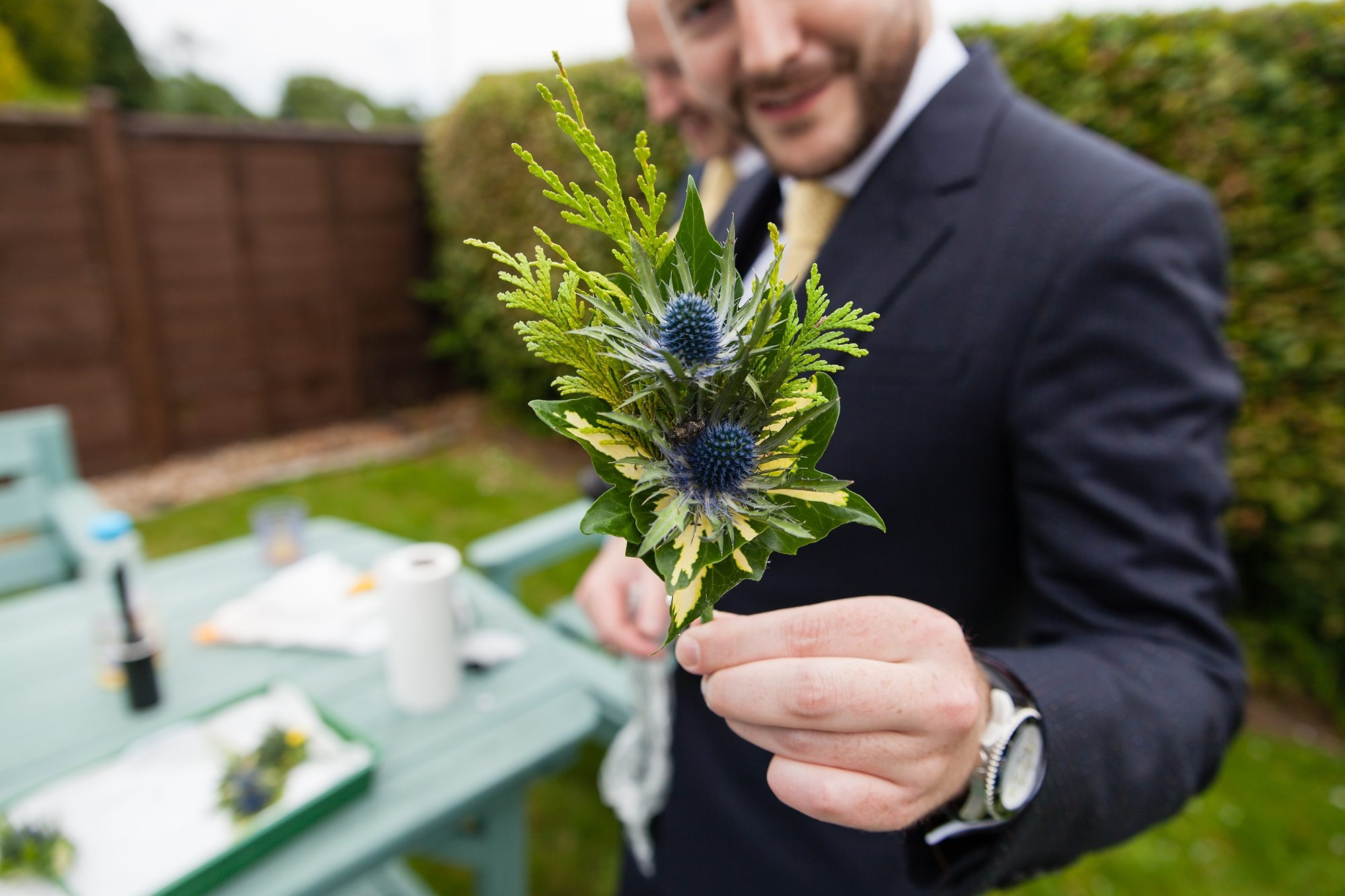 groom holding blue flower in York barn wedding outdoors